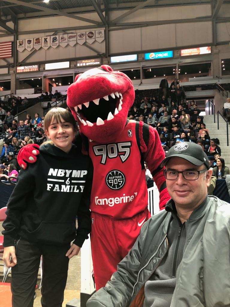 an NBYMP mentee wearing a black NBYMP hoodie stands beside the Toronto Raptor's mascot with a seated adult
